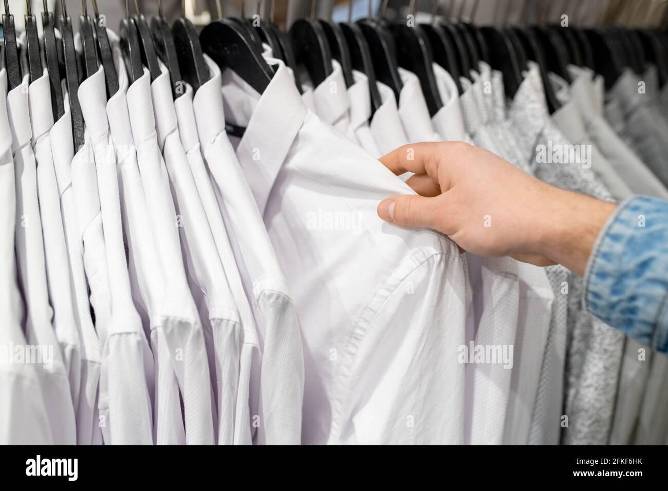 Main de l'acheteur choisissant une chemise blanche dans le magasin de vêtements Banque D'Images