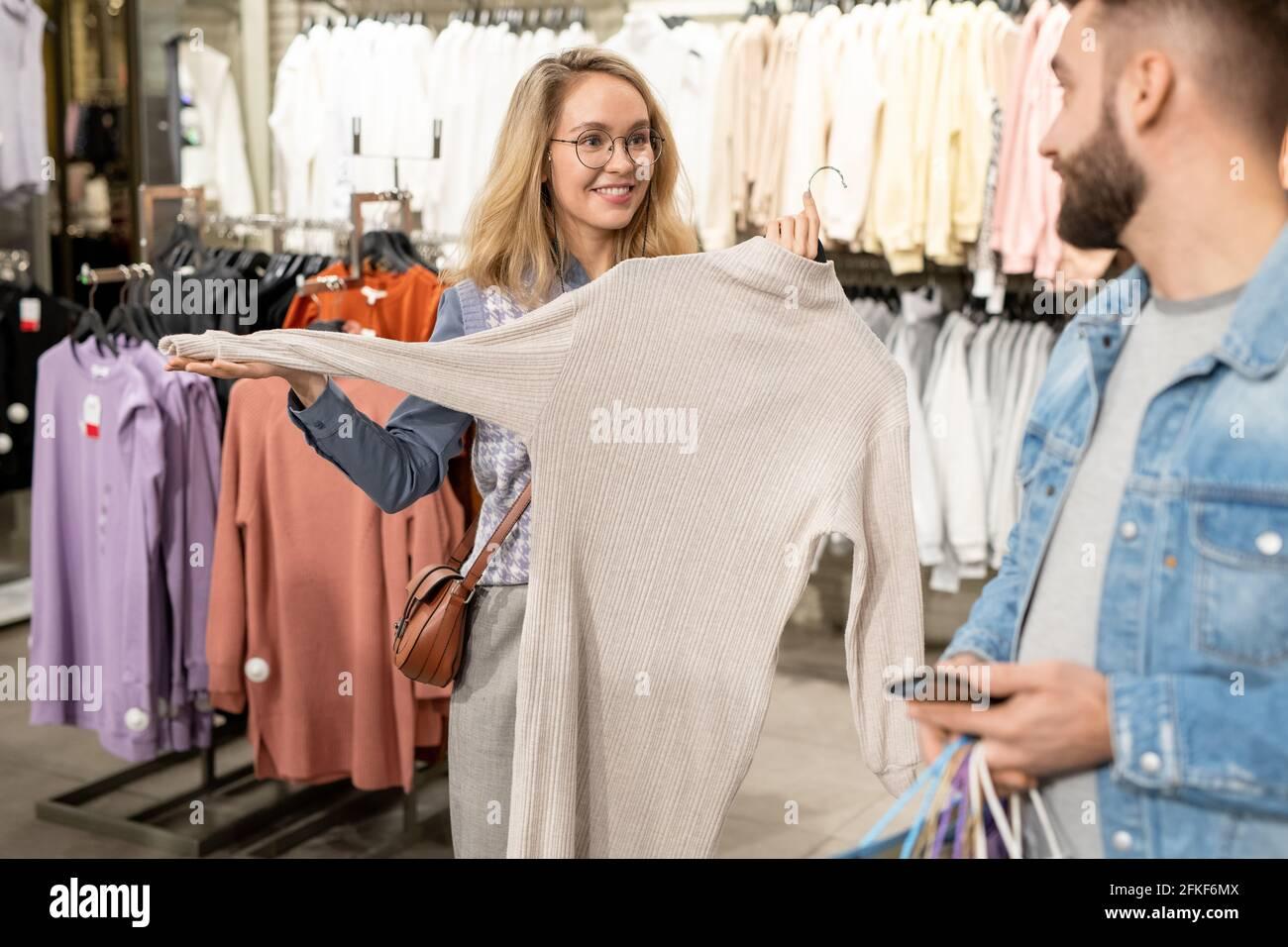 Un homme et une femme choisissant de nouveaux vêtements tout en faisant du shopping Banque D'Images