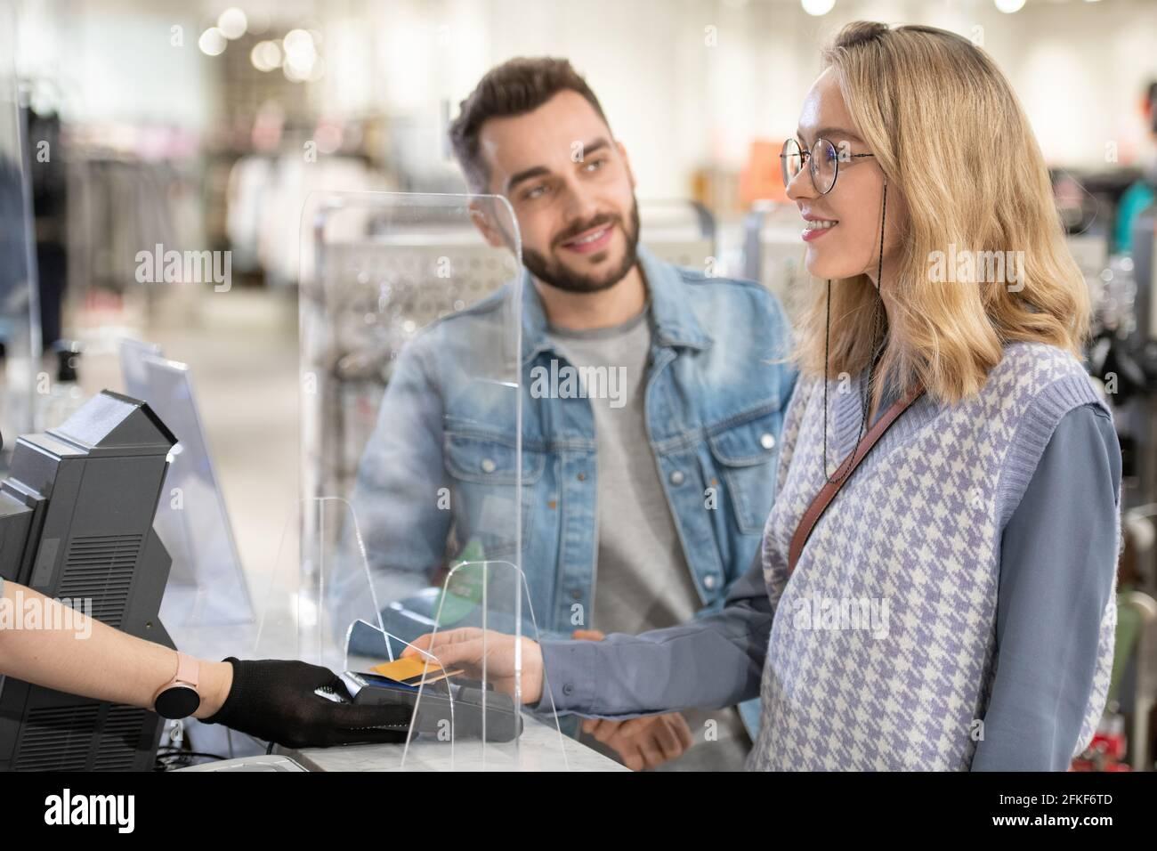 Un homme et une femme qui paient pour les vêtements pendant le shopping dans le grand magasin Banque D'Images
