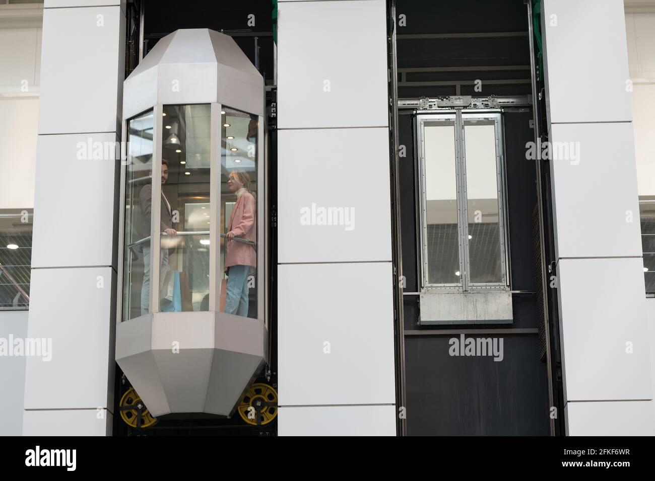 Une personne debout dans un ascenseur en mouvement à l'intérieur d'un grand centre commercial contemporain Banque D'Images