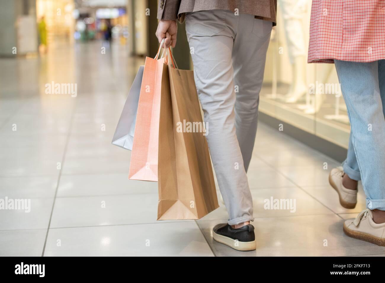 Homme portant des sacs de shopping tout en se déplaçant à l'intérieur du centre commercial Banque D'Images