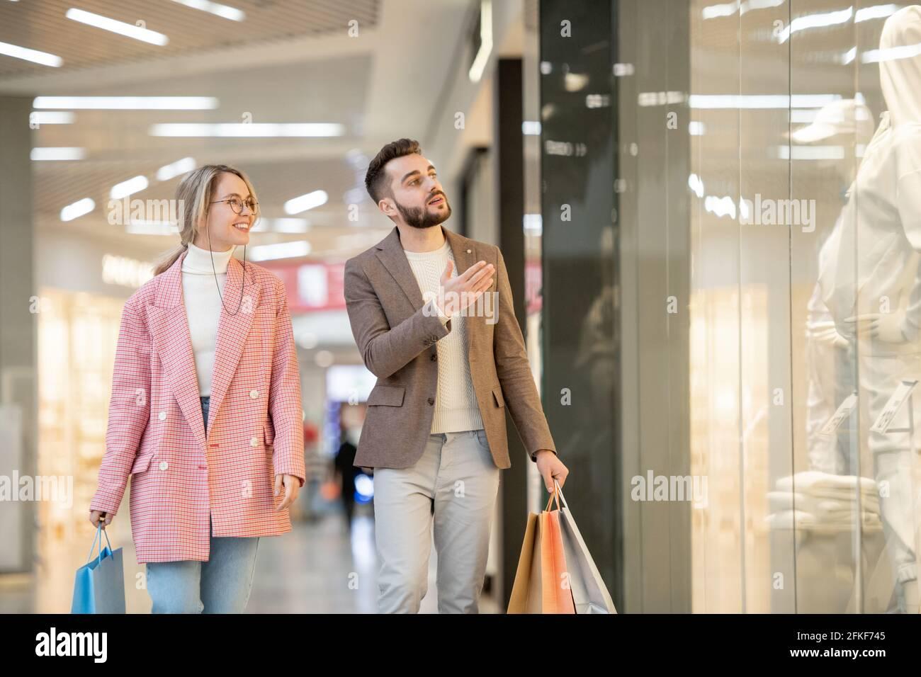 Un homme et une femme qui magasinent dans un centre commercial contemporain Banque D'Images