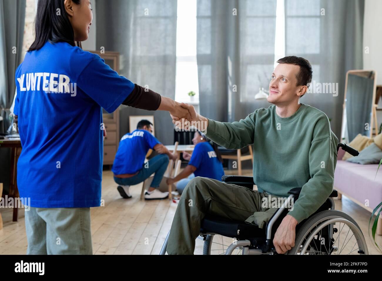 Une jeune femme volontaire se secouant la main de l'homme dans un fauteuil roulant Banque D'Images