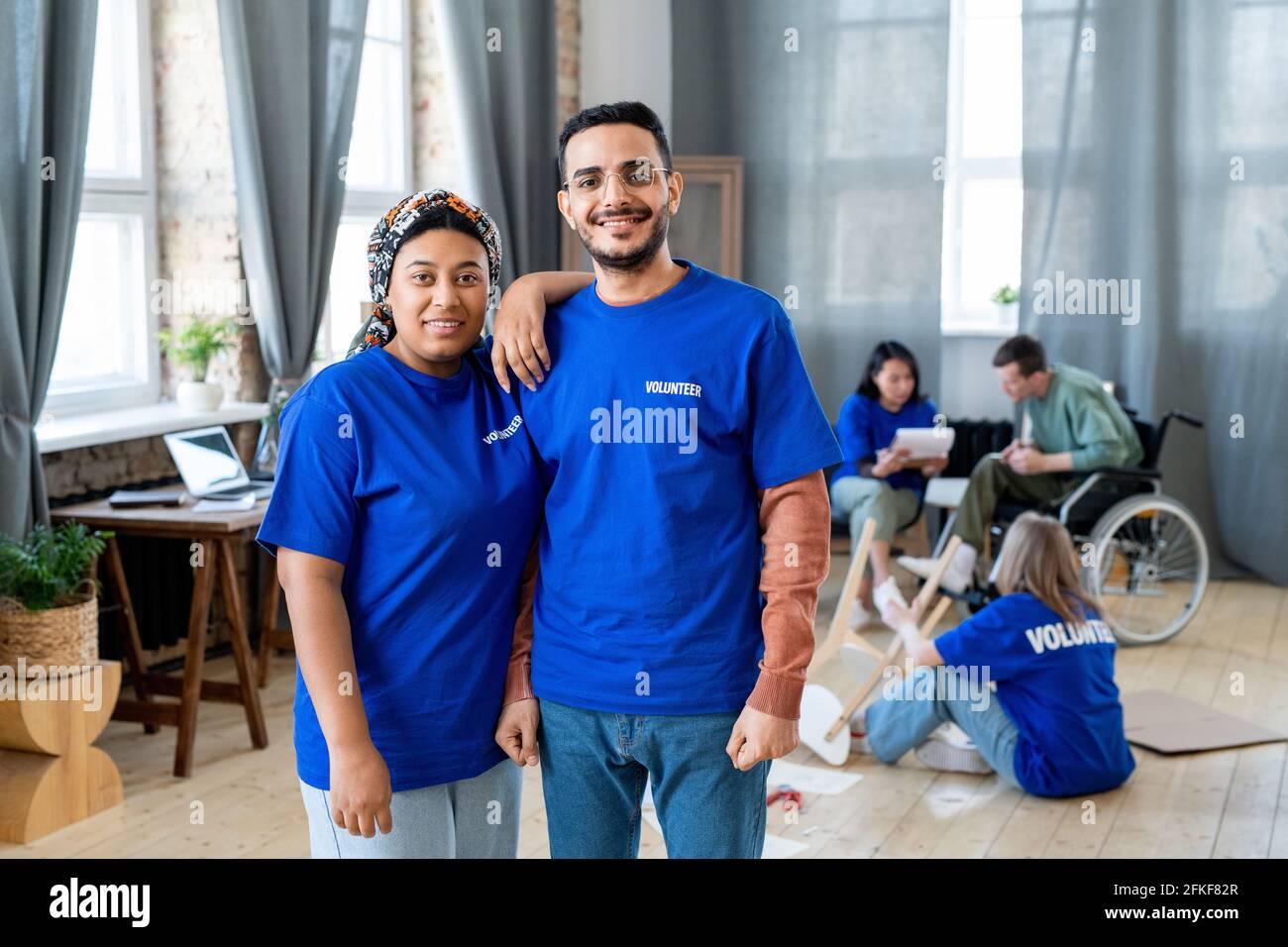 Un groupe de jeunes interculturels heureux en t-shirts bleus poser pour une photo Banque D'Images