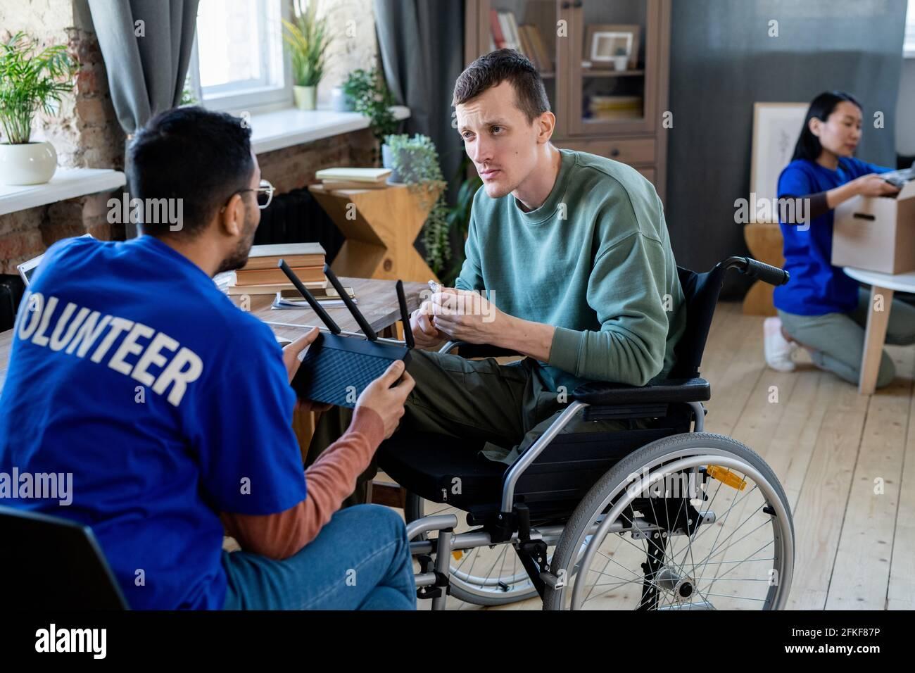 Deux jeunes hommes parlent pendant que l'un d'eux est assis fauteuil roulant Banque D'Images