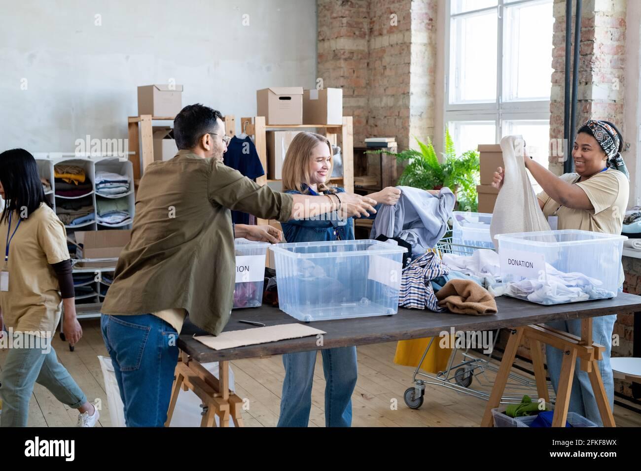 Les femmes heureuses choisissent des vêtements de don dans des récipients sur la table Banque D'Images