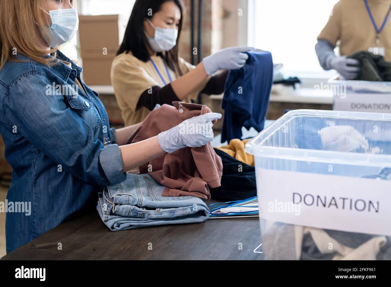 Jeune femme en gants et masque dépliante t-shirt sur la table Banque D'Images