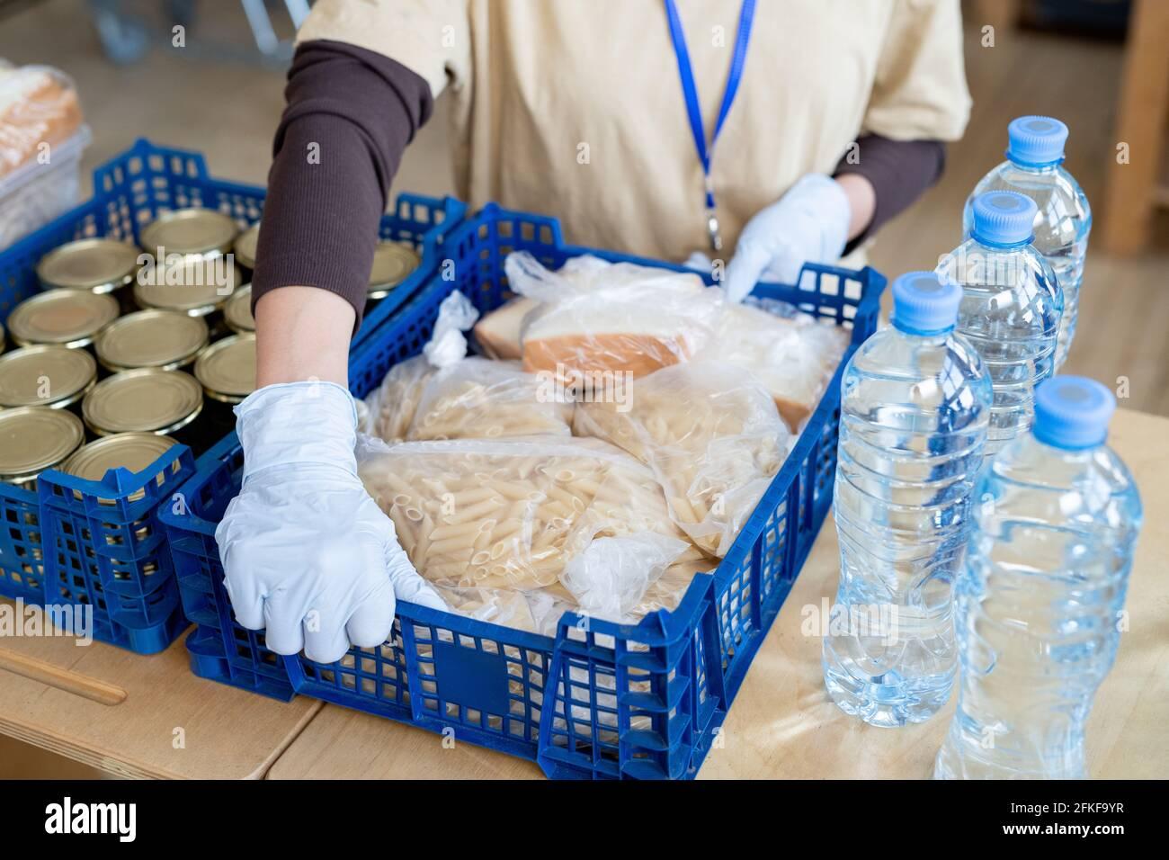 Un volontaire ganté met une grande boîte contenant des produits alimentaires sur la table Banque D'Images