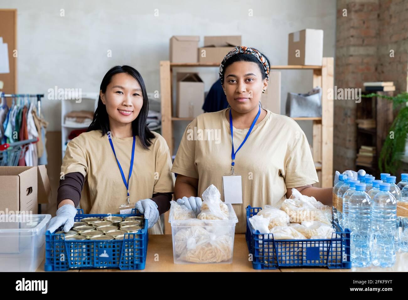 Deux jeunes femmes bénévoles debout à table avec de la nourriture gratuite dans des boîtes en plastique Banque D'Images