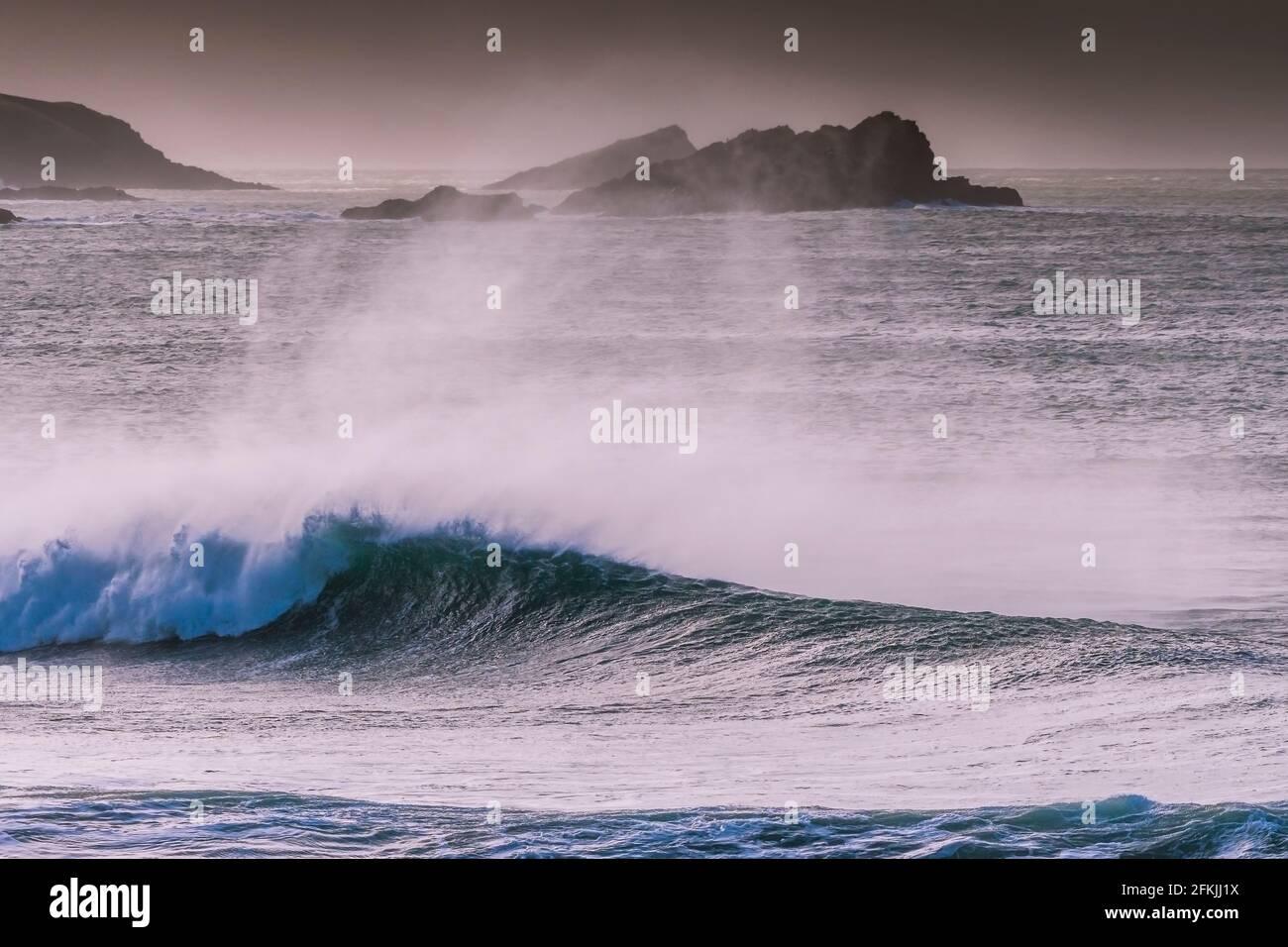Une forte pulvérisation de vent au large d'une grande vague dans la baie de Fistral, à Newquay, dans les Cornouailles. Banque D'Images