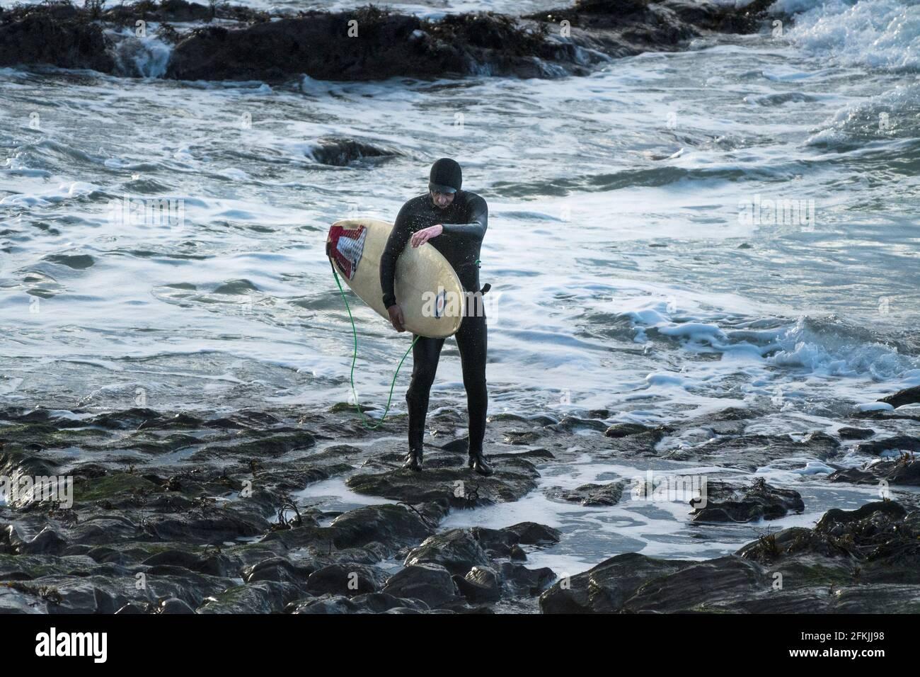 Un surfeur transportant sa planche de surf et marchant hors de la mer à Little Fistral à Newquay en Cornouailles. Banque D'Images