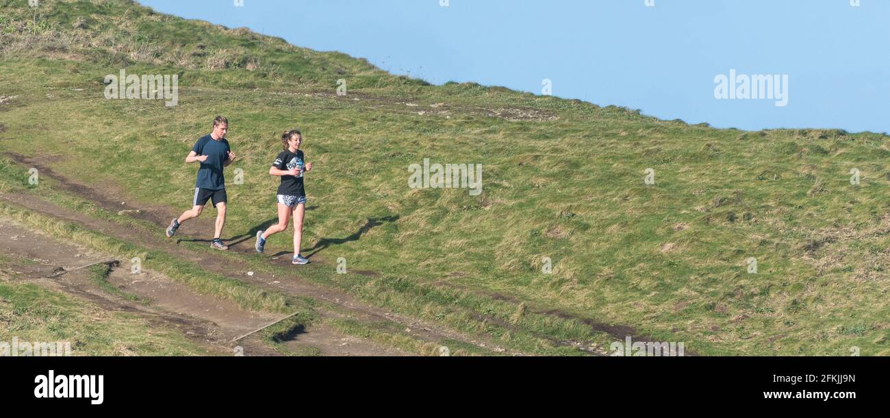 Image panoramique d'un coureur mâle et d'une femelle sur un sentier de Towan Head à Newquay, en Cornouailles. Banque D'Images