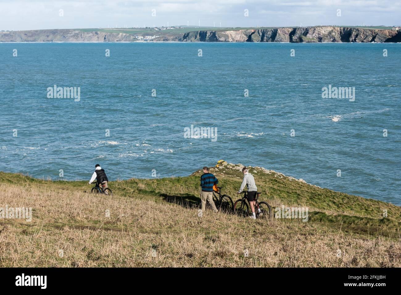 Trois jeunes hommes poussent des bicyclettes le long d'un sentier sur Towan Head, surplombant la baie de Newquay, dans les Cornouailles. Banque D'Images
