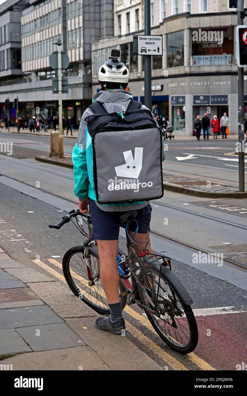 Deliveroo cycliste attendant sur Princes Street, Édimbourg, Écosse, Royaume-Uni. Banque D'Images