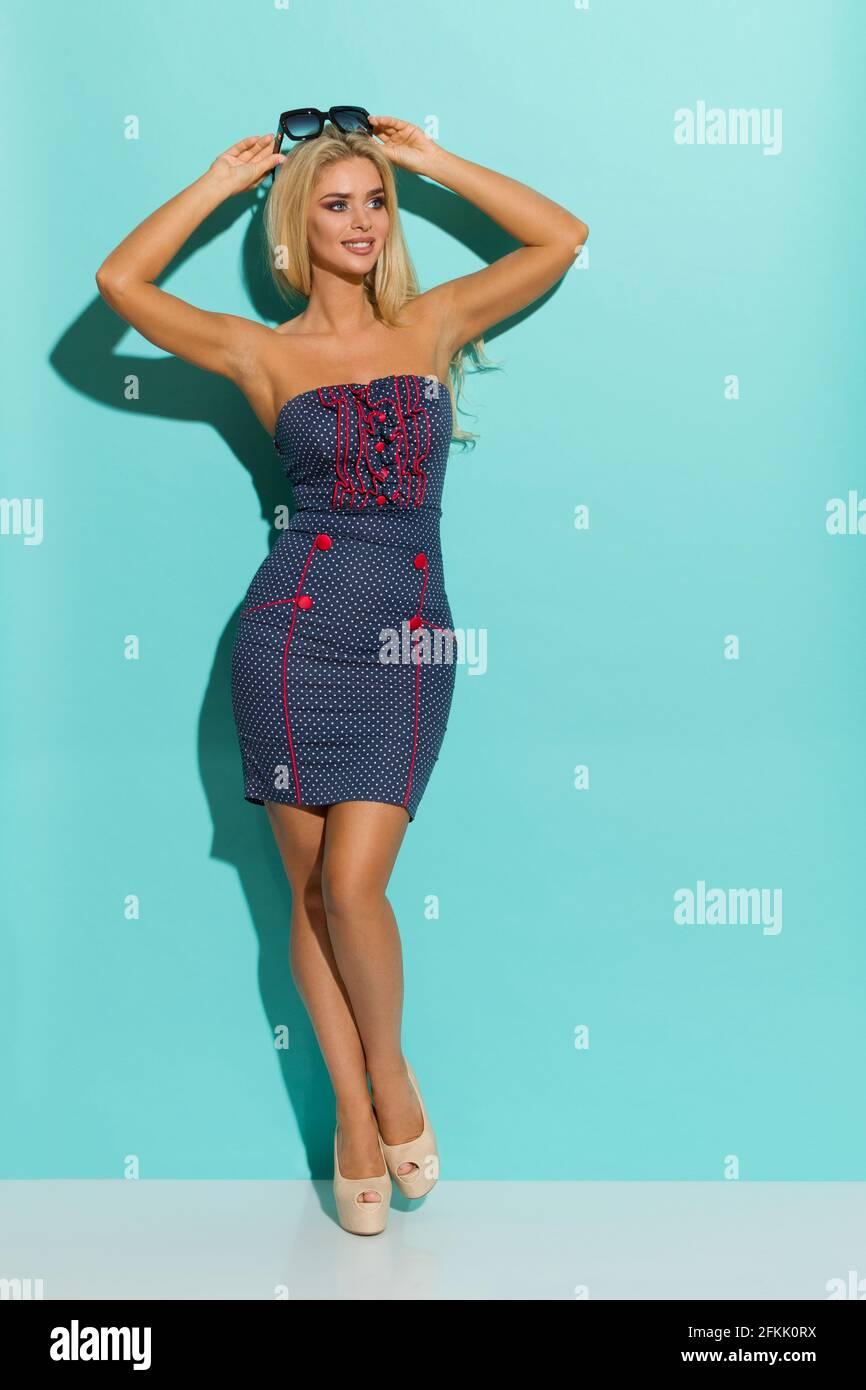 Belle femme blonde en bleu pointillé mini robe nad talons hauts tient des lunettes de soleil sur la tête et regarde loin. Plein studio tourné sur turquoise Banque D'Images