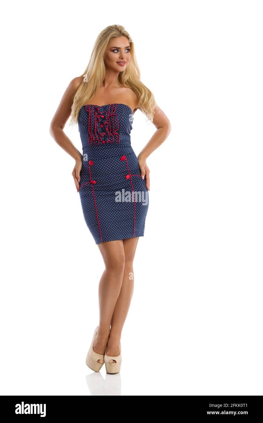 Belle femme blonde en bleu pointillé mini robe et talons hauts pose avec les mains sur la hanche et regarder loin. Prise de vue en studio sur toute la longueur isolée sur blanc Banque D'Images