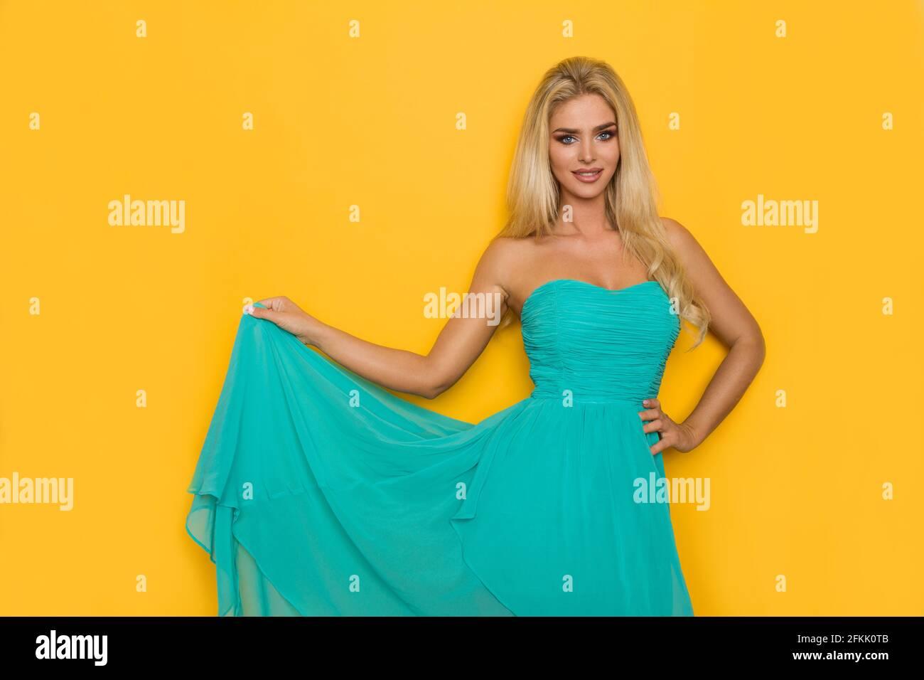 Belle femme blonde pose dans la robe tuquoise et regarde la caméra. Trois quarts de long studio tourné sur fond jaune. Banque D'Images