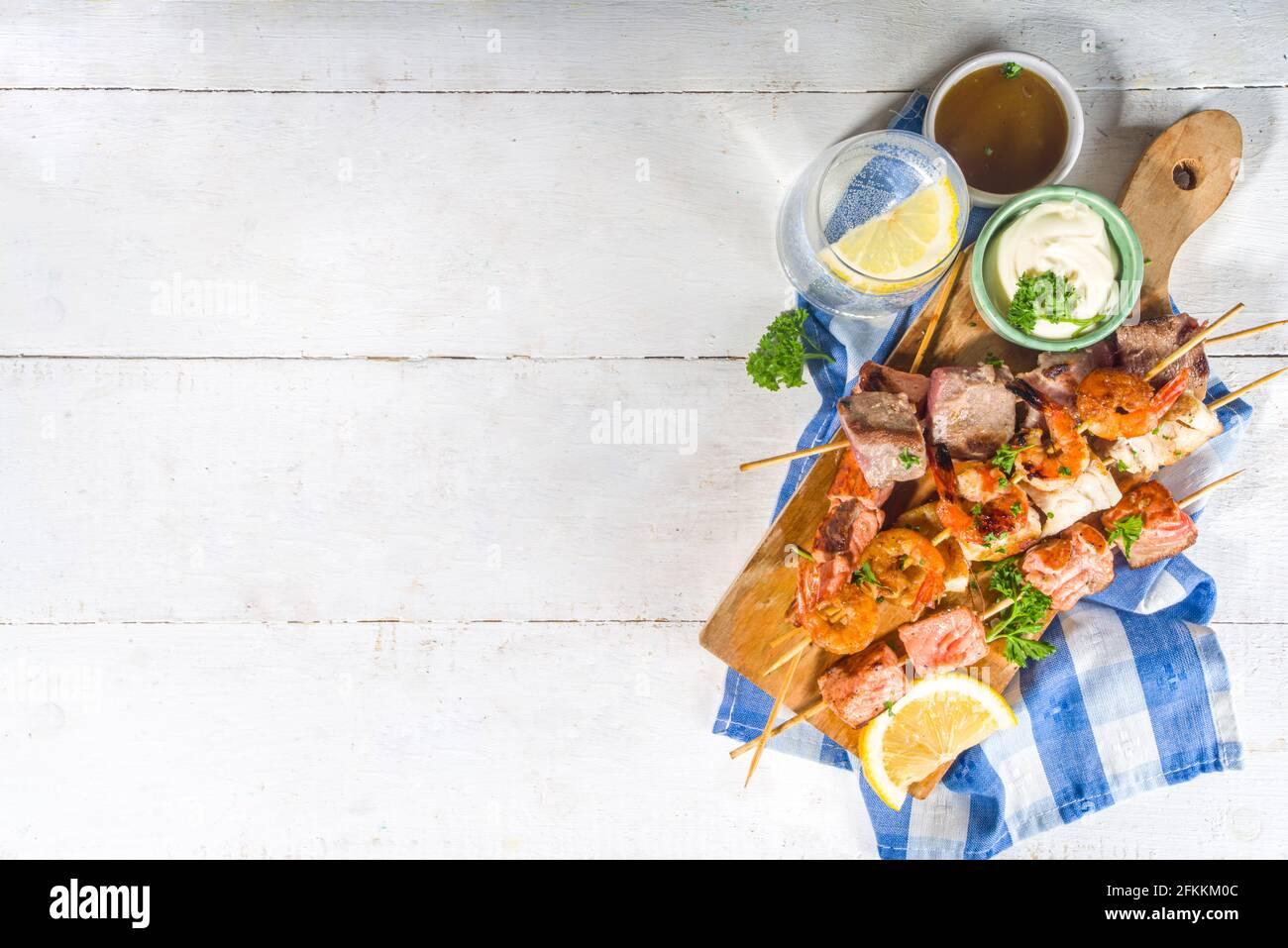 Assortiment divers barbecue cuisine méditerranéenne - poisson, crevettes, crabe, moules, kebabs avec sauces, arrière-plan en bois blanc, au-dessus de l'espace de copie Banque D'Images