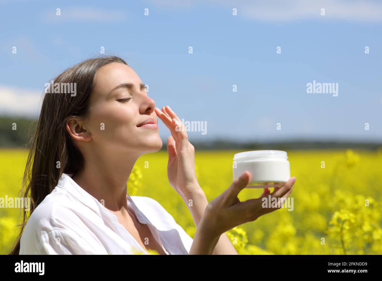 Femme de beauté tenant le pot appliquant la crème hydratante sur le visage dans un champ fleuri Banque D'Images
