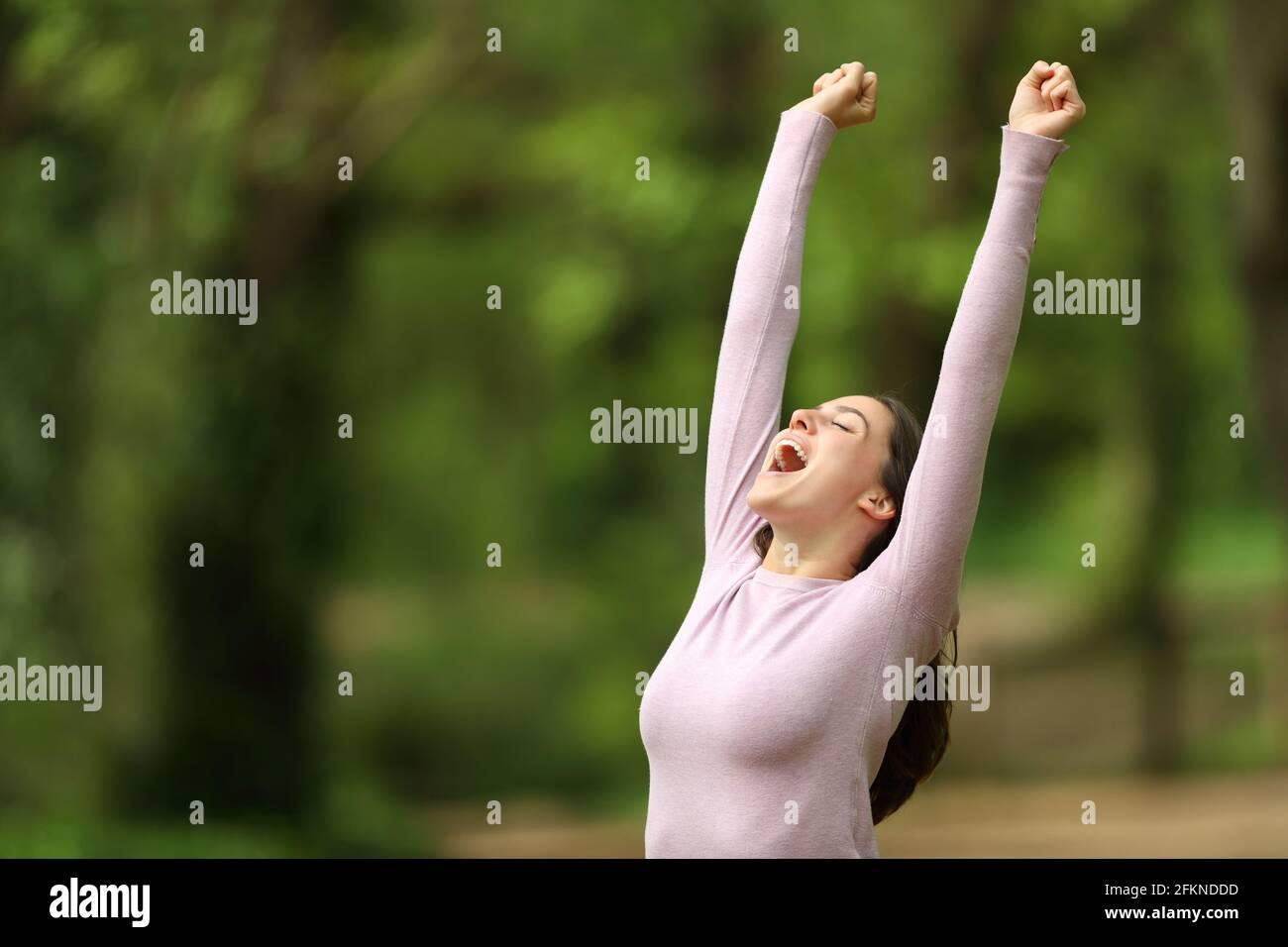 Une femme excitée se levant les bras et hurlant à célébrer dans un vert forêt Banque D'Images