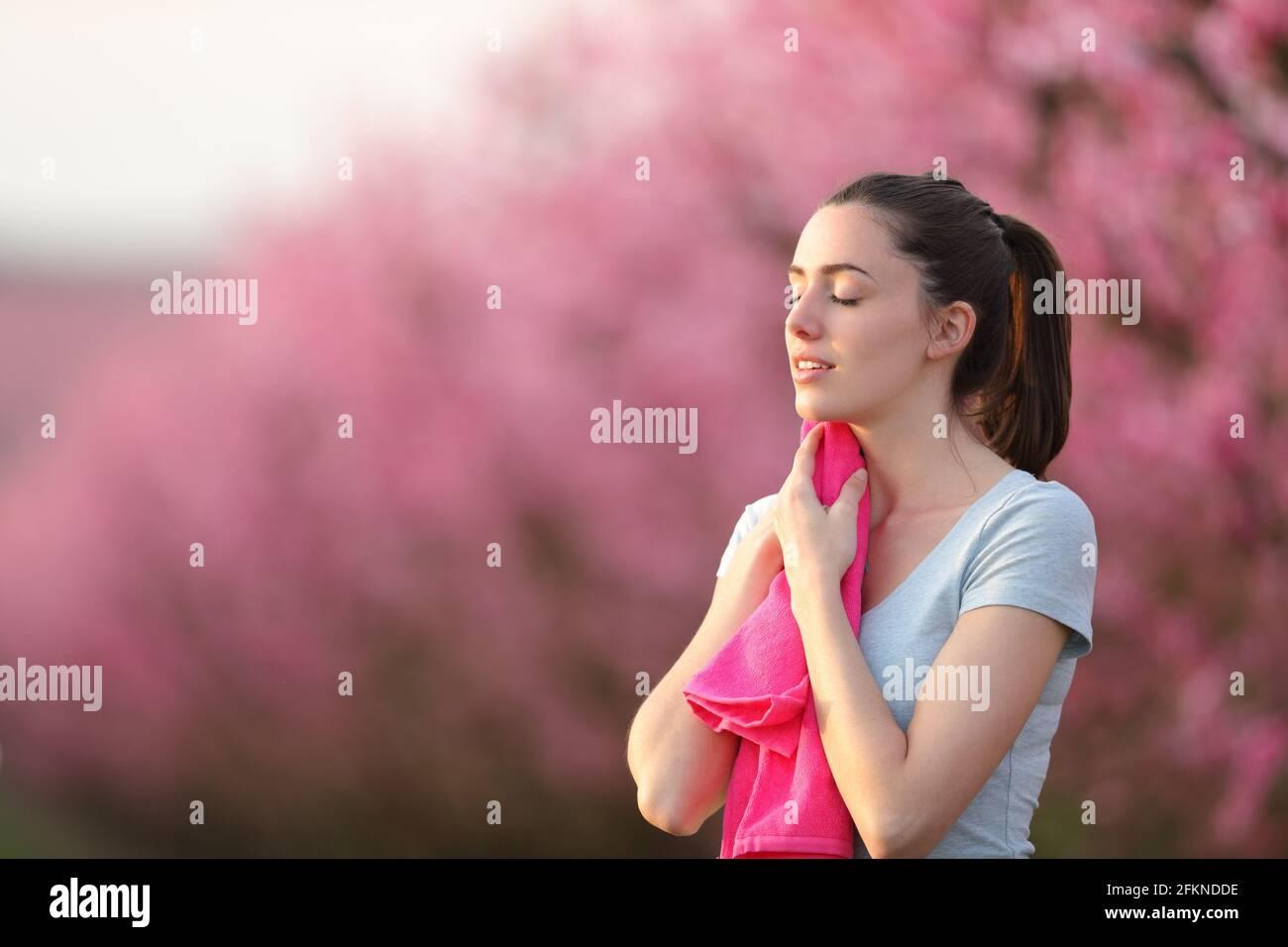 Le coureur épuisé sèche la sueur avec une serviette rose après la course dans un champ Banque D'Images