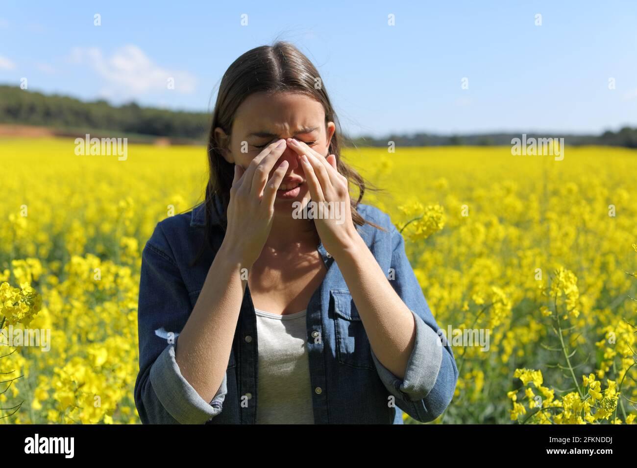 Femme allergique se grattant les yeux qui démangent au printemps en a champ à fleurs jaunes Banque D'Images