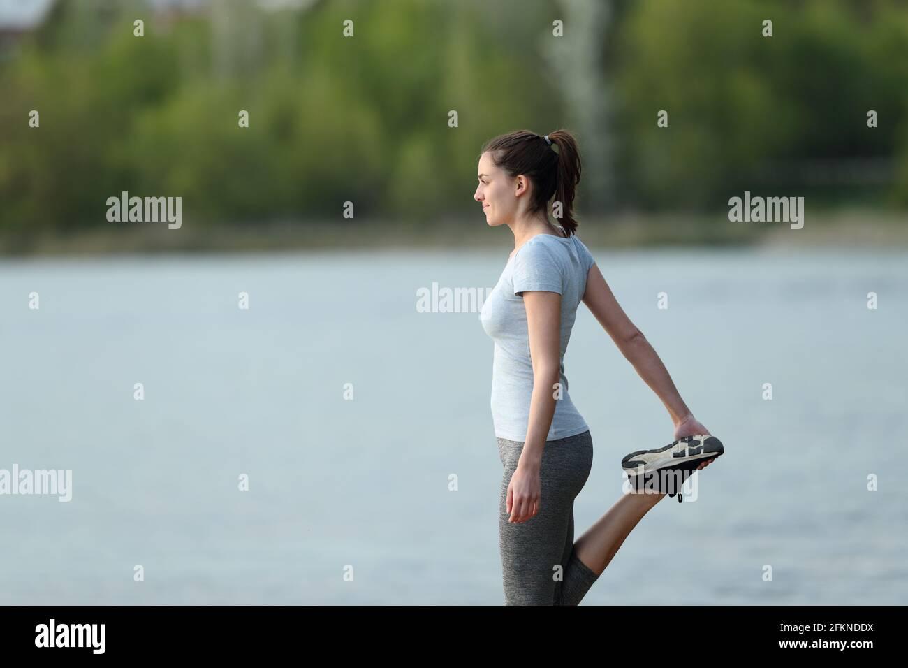Vue latérale d'une sportswoman qui s'étire la jambe après le sport dans un lac Banque D'Images