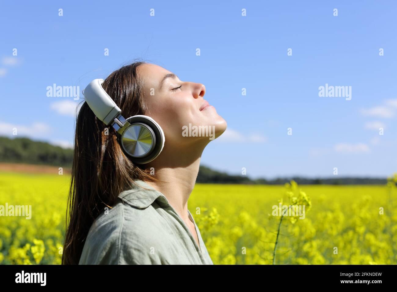 Portrait d'une femme heureuse méditant avec la technologie sans fil casque dans un champ jaune Banque D'Images