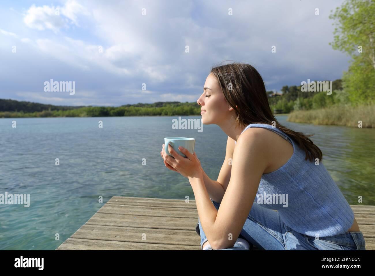 Profil d'une femme qui se détend en buvant du café dans un lac jetée Banque D'Images