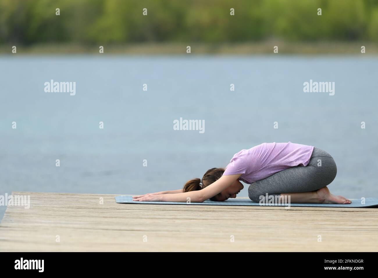 Profil d'un yogi faisant de l'exercice de yoga dans un lac jetée Banque D'Images