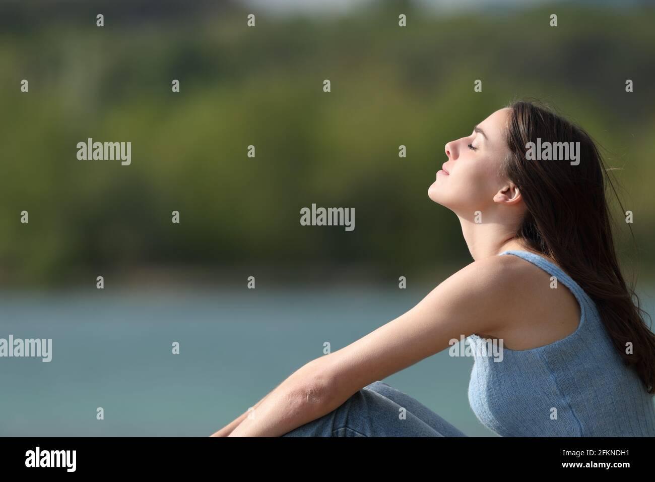 Vue latérale d'une femme détendue qui respire fraîche air dans un lac Banque D'Images