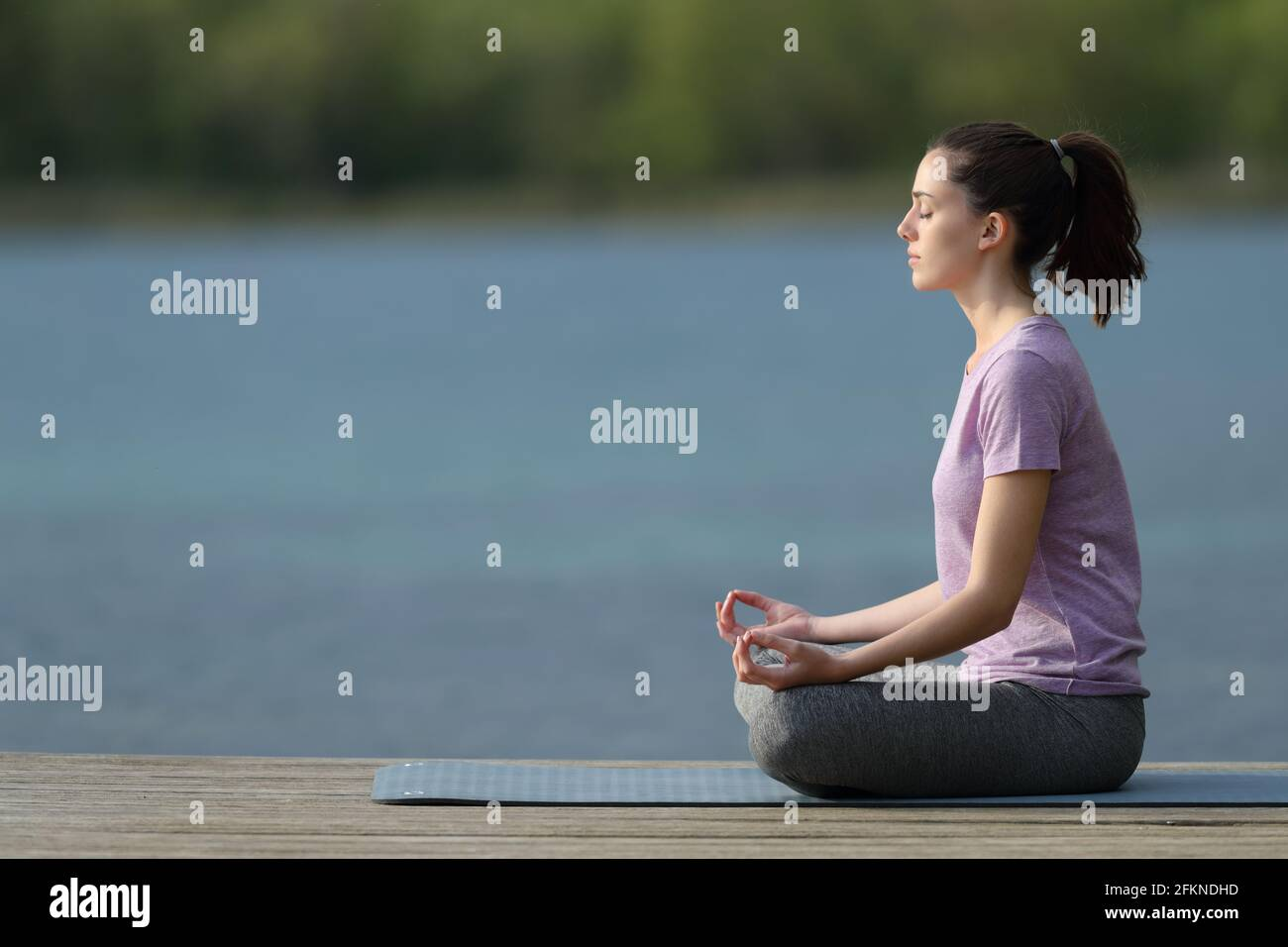 Profil d'un yogi pratiquant le yoga dans un quai à côté un lac Banque D'Images