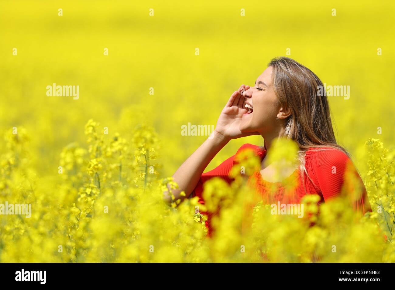 Bonne femme criant avec la main sur la bouche dans un jaune champ au printemps Banque D'Images