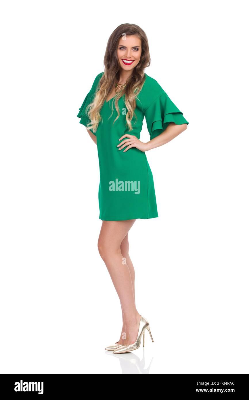 Souriante jeune femme en vert mini robe et or talons hauts pose avec les mains sur la hanche. Prise de vue en studio sur toute la longueur isolée sur blanc. Banque D'Images