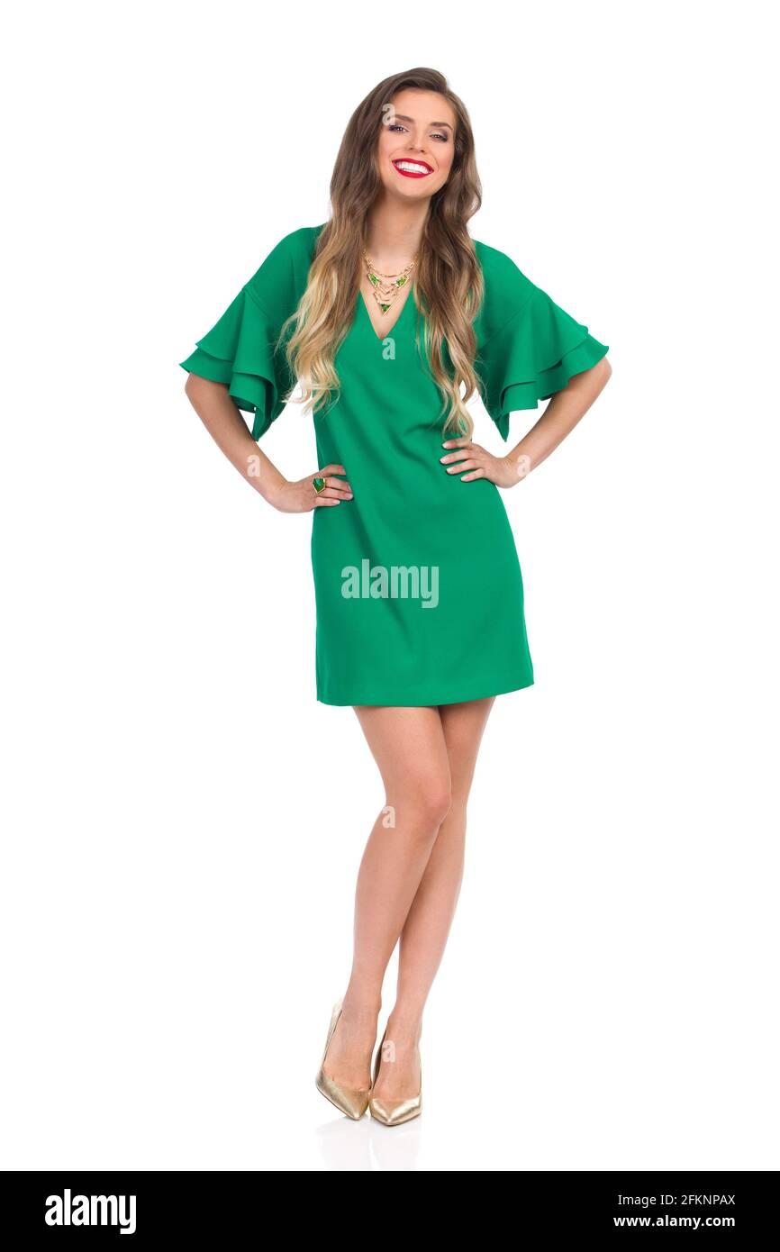 Confiante jeune femme en vert mini robe et or talons hauts est debout avec les mains sur la hanche et sourire. Vue avant. Prise de vue en studio pleine longueur isolée Banque D'Images