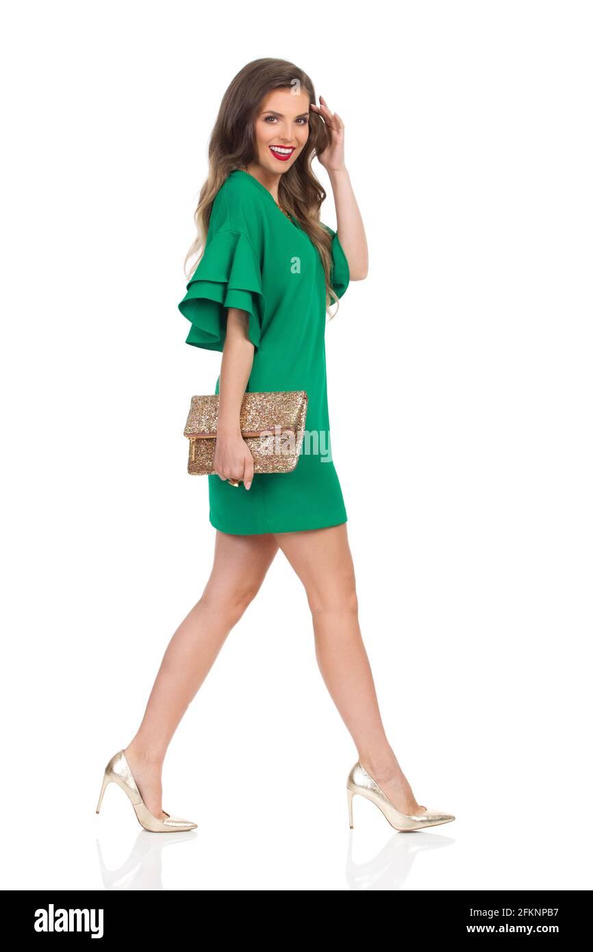 Belle jeune femme marche dans vert mini robe et talons hauts, tenant l'or pochette porte-monnaie, regardant l'appareil photo et sourire. Vue latérale. Longueur totale Banque D'Images
