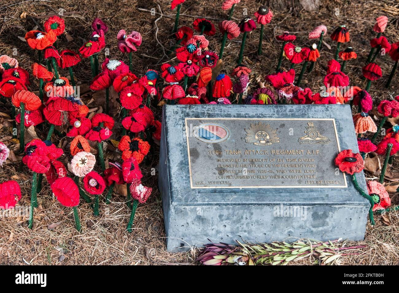 Plaque du mémorial de guerre placée sur le domaine de Kings pour honorer le 106e Tank Attack Regiment A.I.F., avec des coquelicots tricotés, Melbourne, Australie Banque D'Images