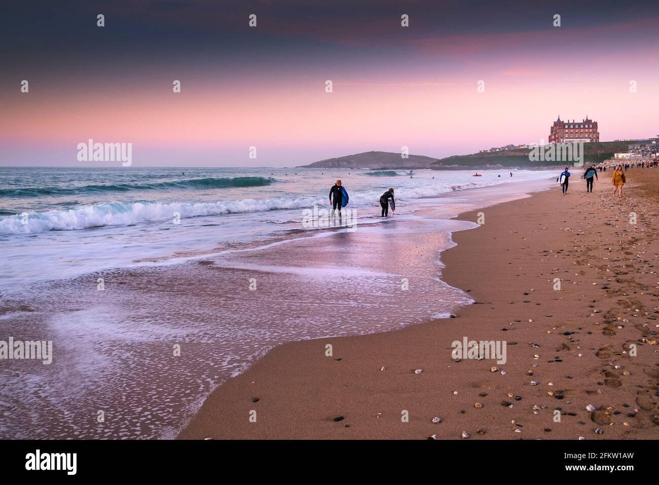 Coucher de soleil sur les surfeurs marchant dans la mer à Fistral Beach à Newquay dans les Cornouailles. Banque D'Images