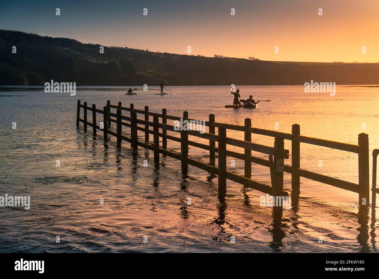 Coucher de soleil doré sur les personnes pagayant des kayaks et stand Up Paddleboard sur la rivière Gannel à marée haute à Newquay dans les Cornouailles. Banque D'Images