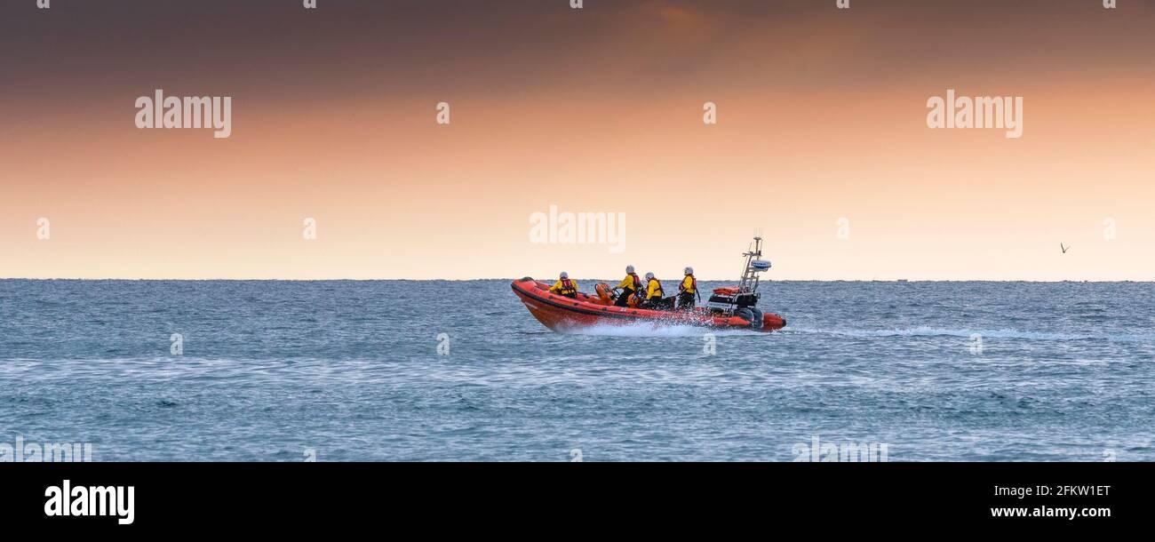 Une image panoramique de RNLI Gladys Mildred, le bateau de sauvetage Atlantic 85 de Newquay répondant à un callout d'urgence à la fin de la journée à Fistral Bay, en Co Banque D'Images
