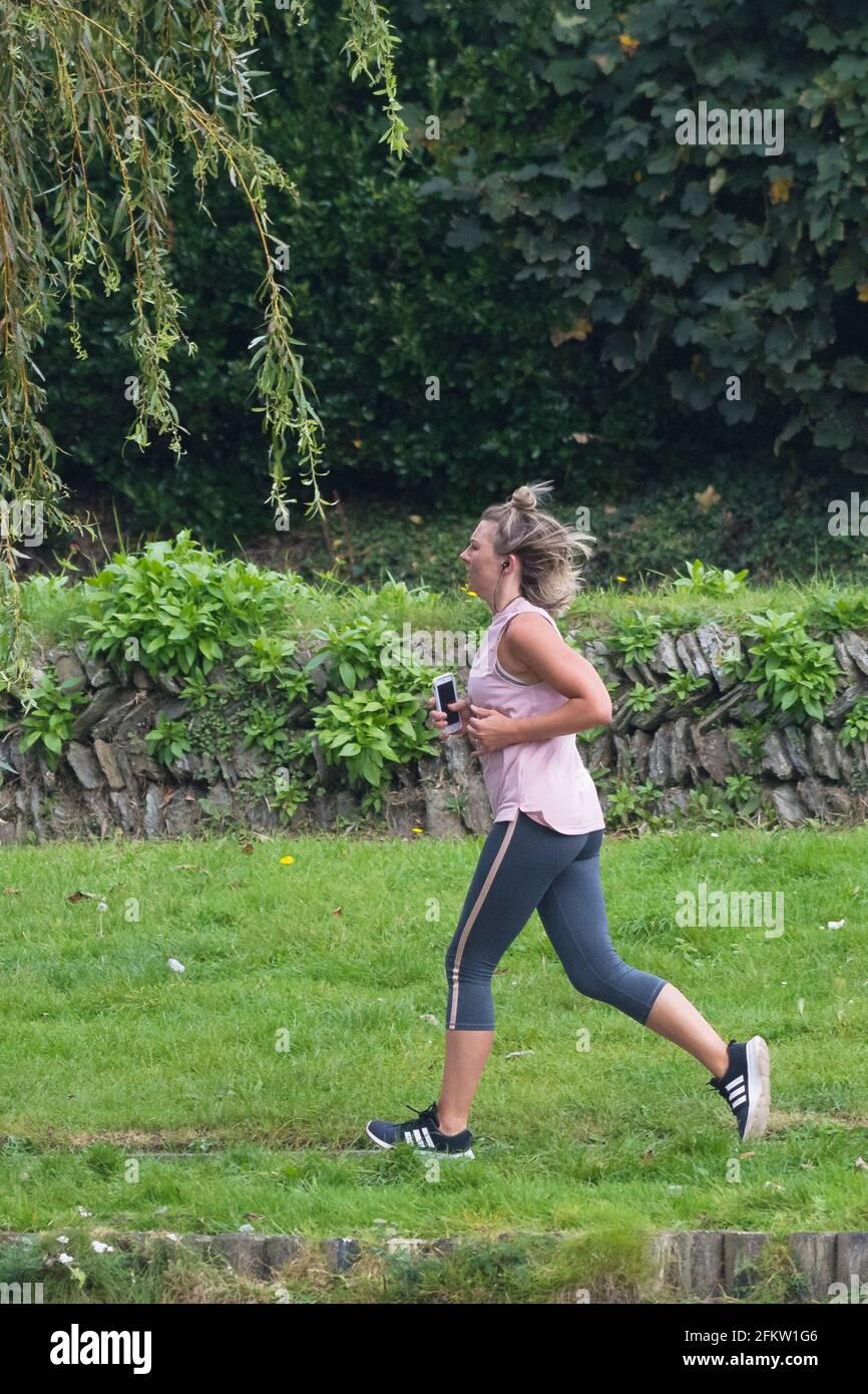 Une femme qui court dans un parc. Banque D'Images