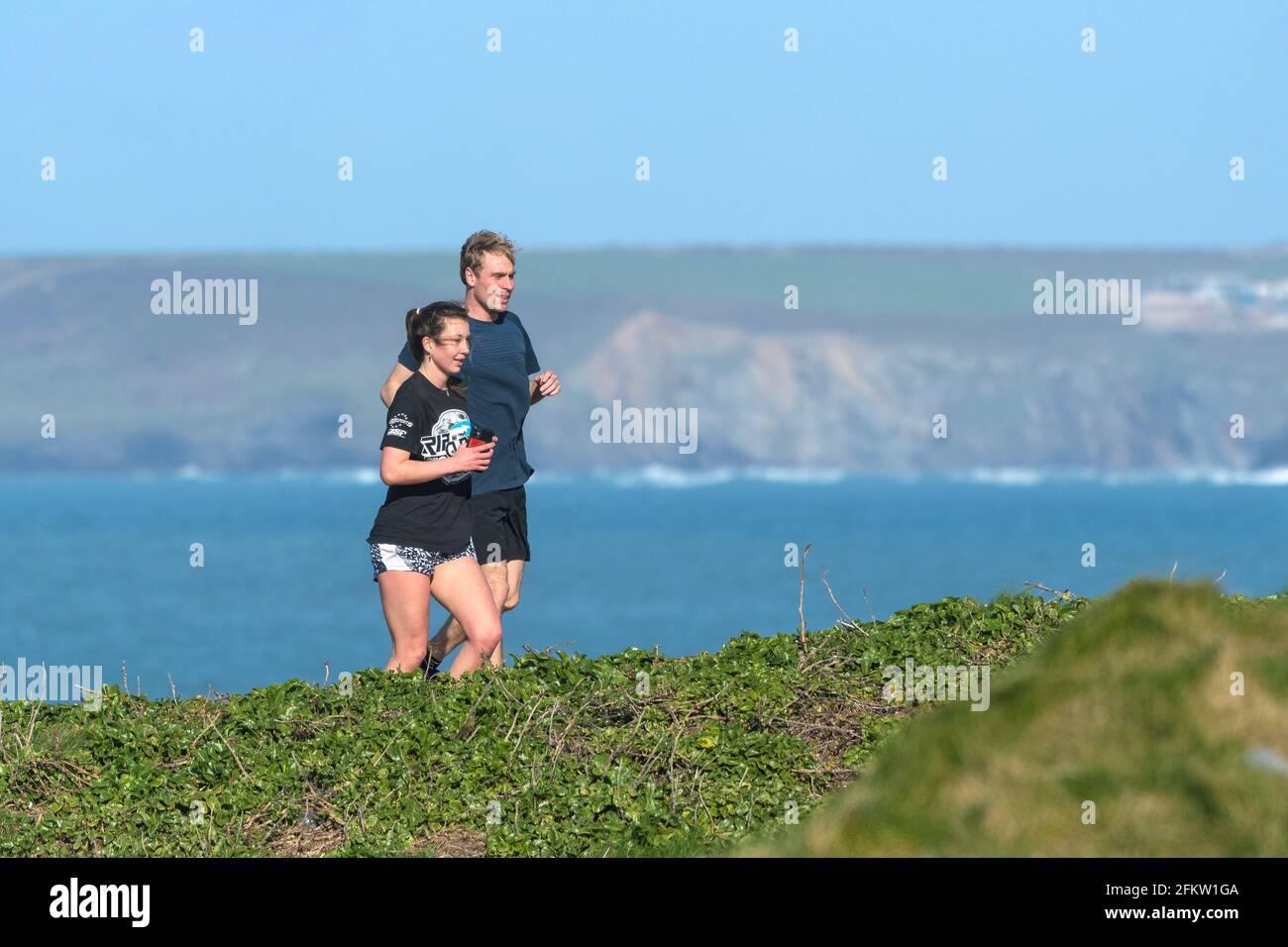 Un coureur mâle et un coureur femelle sur le sentier côtier de Newquay, en Cornouailles. Banque D'Images