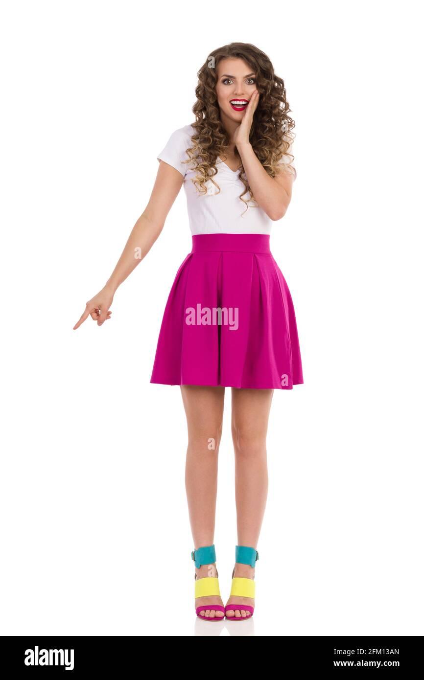 Une jeune femme excitée avec des talons hauts colorés, une mini jupe rose et un haut blanc est debout, tenant la main sur le menton et pointant vers le bas. Vue avant. Longueur totale Banque D'Images