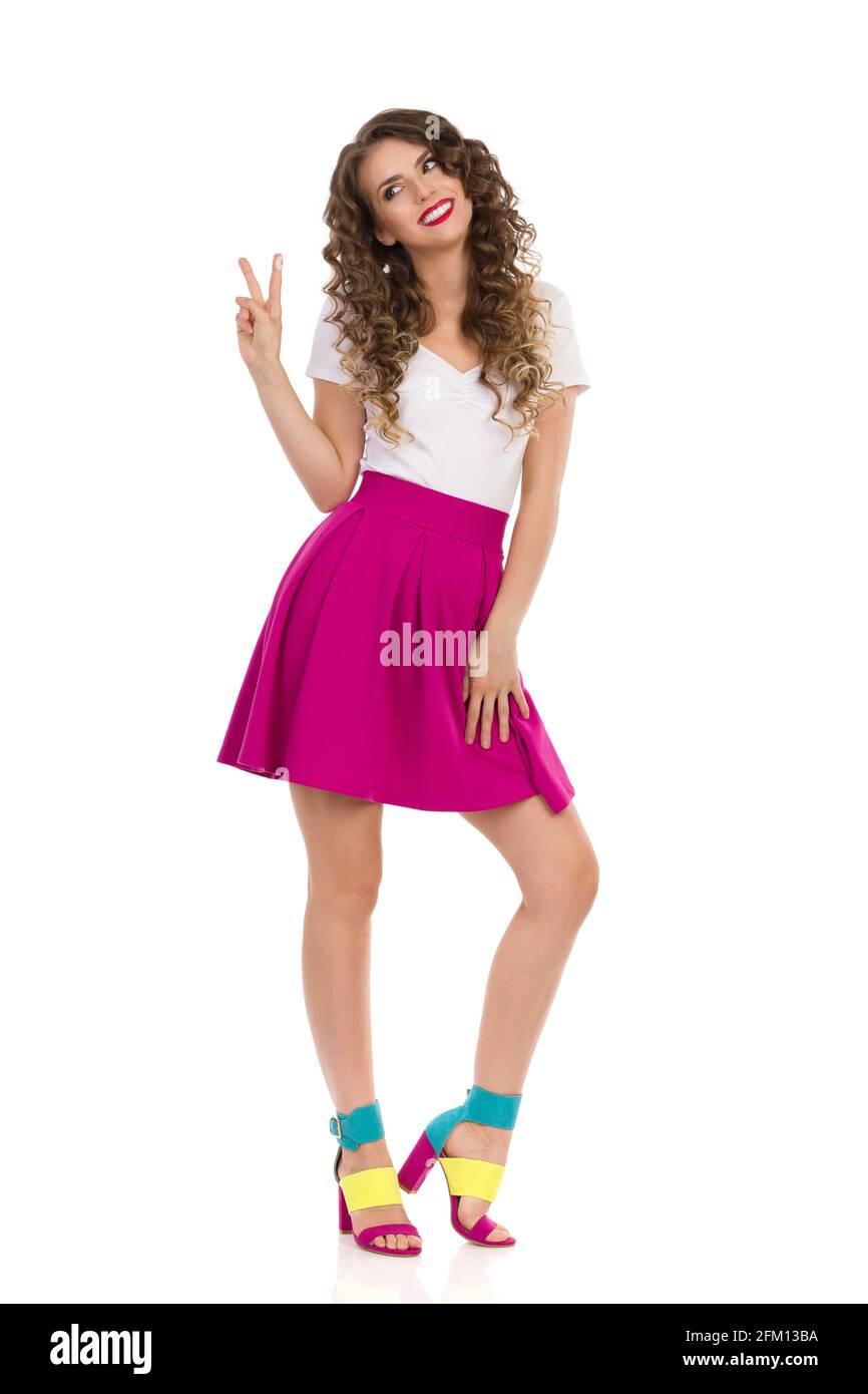 Jolie femme dans les hauts talons hauts colorés, mini jupe rose et le haut blanc est debout, montrant le signe de la main de paix et regardant loin. Vue avant. Studio complet Banque D'Images