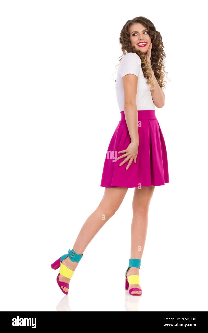 Bonne jeune femme aux talons hauts colorés, mini jupe rose et haut blanc est debout, tenant la main sur le menton et regardant loin par-dessus l'épaule. Vue avant. Banque D'Images