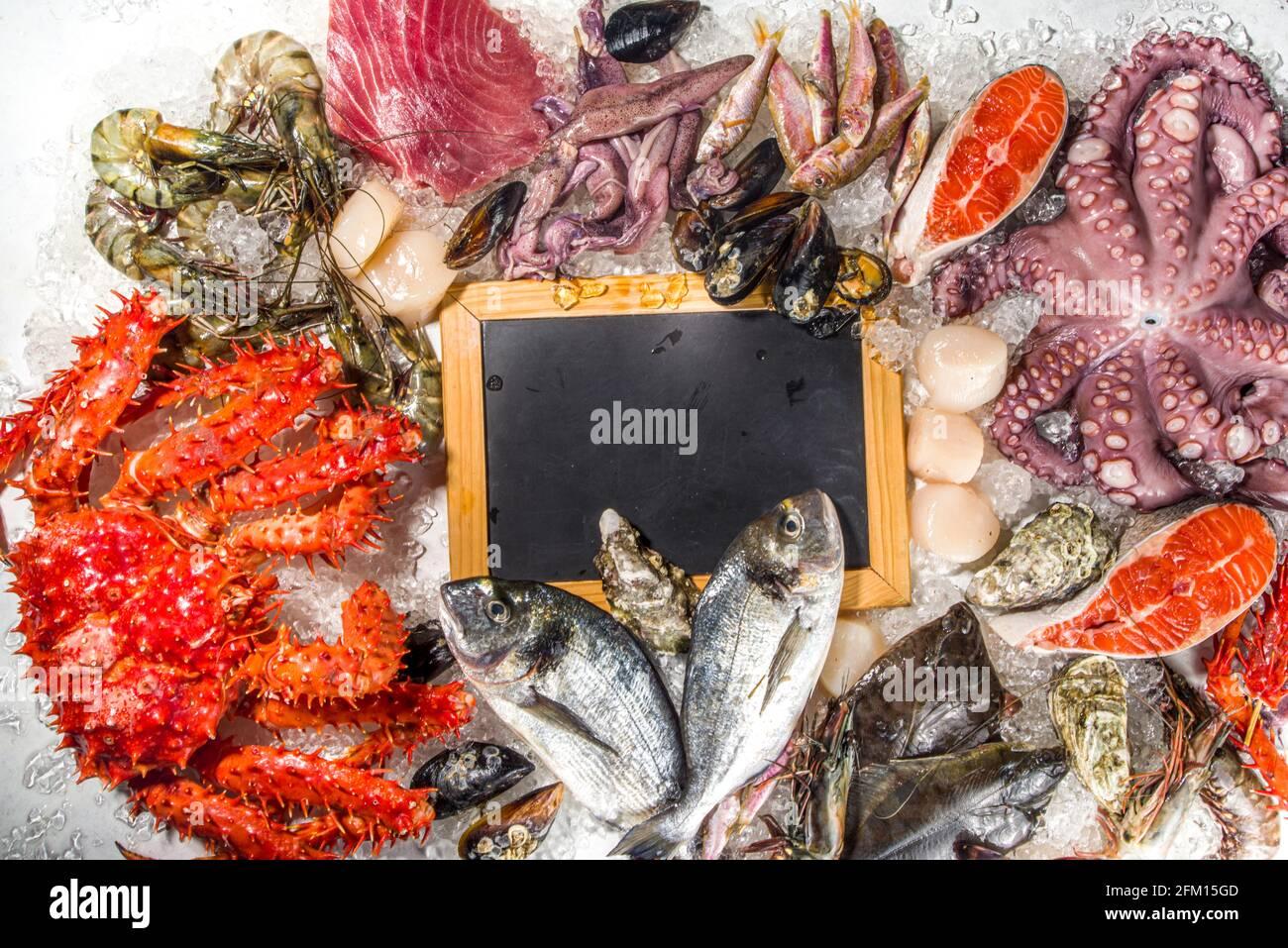 Ensemble de divers fruits de mer frais crus - pieuvre, crabe, calmar, crevettes, huître, moules, saumon thon dorada poisson avec épices d'herbes citron, dos blanc Banque D'Images
