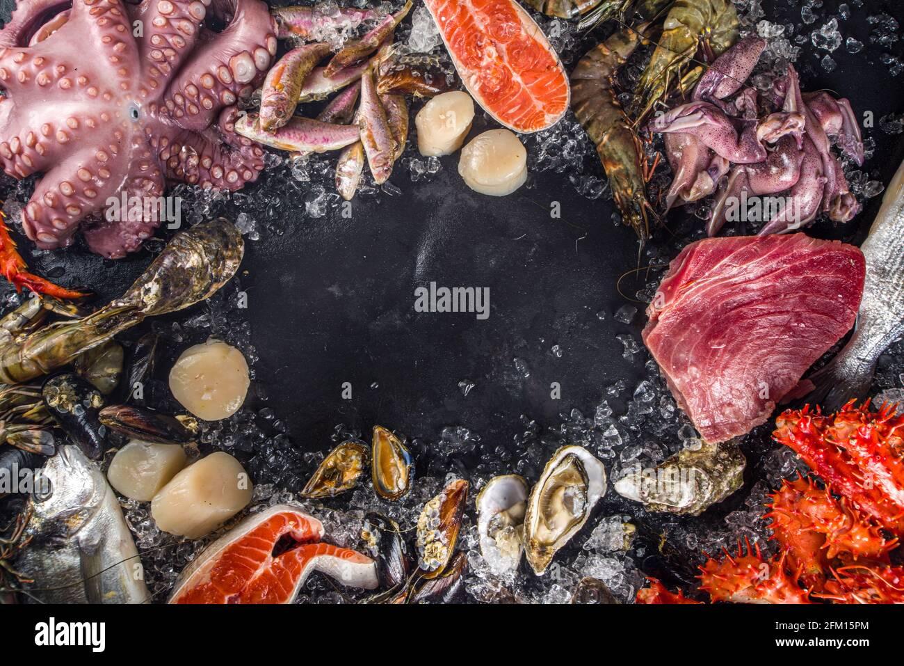Ensemble de divers fruits de mer frais crus - pieuvre, crabe, calmar, crevettes, huître, moules, saumon thon dorada poisson avec épices d'herbes citron, dos noir Banque D'Images