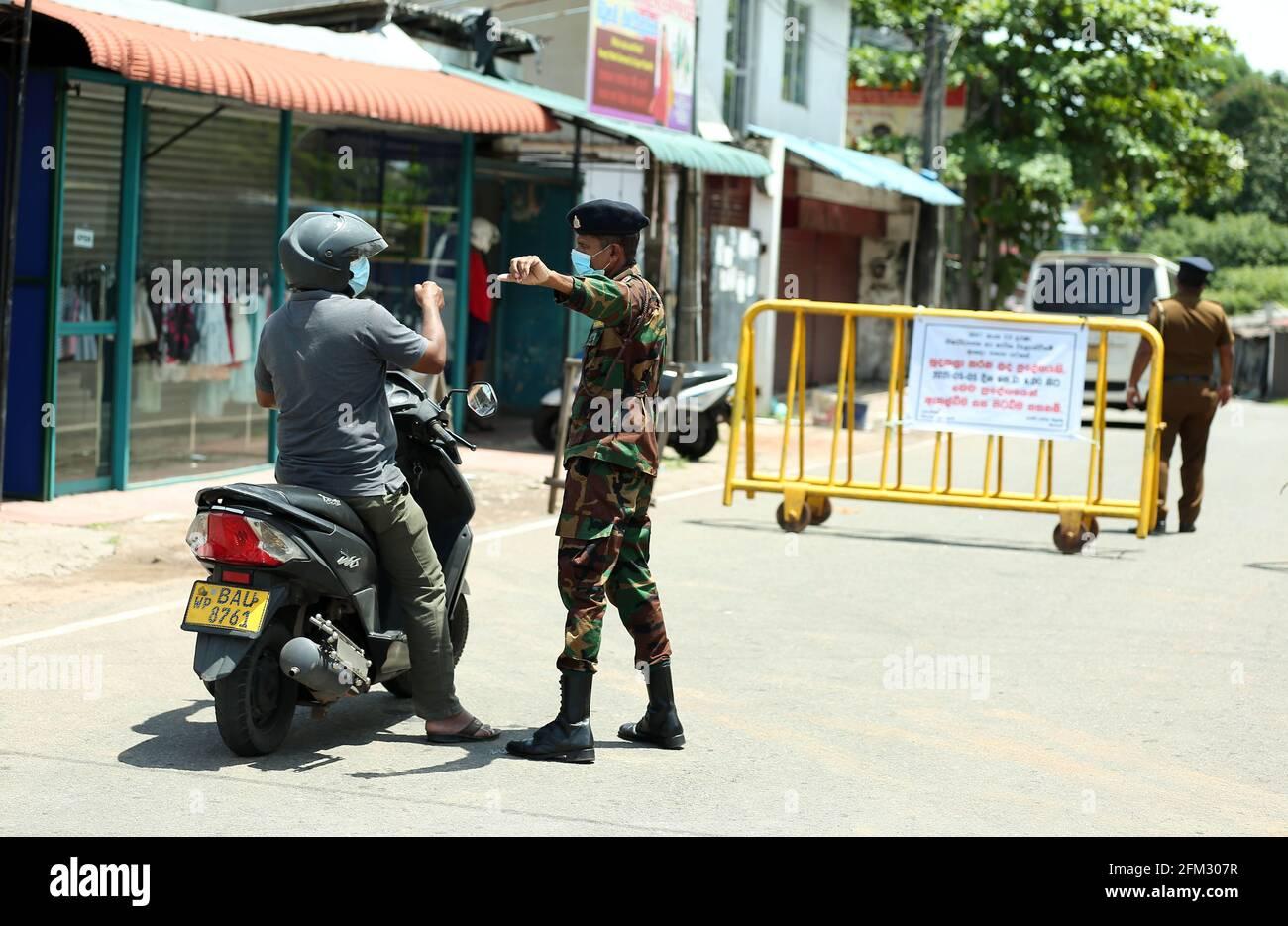 Colombo, Sri Lanka. 5 mai 2021. Un membre de l'armée parle à un homme à côté de barricades établies à Maharagama, alors que les autorités sanitaires ont déclaré la zone à isoler, à Colombo, au Sri Lanka, le 5 mai 2021. Le nombre total de patients infectés par le COVID-19 au Sri Lanka a dépassé la barre des 115,000 mercredi après que plus de 1,800 nouveaux patients ont été identifiés un jour plus tôt, ont montré les statistiques du ministère de la Santé. Crédit: Ajith Perera/Xinhua/Alamy Live News Banque D'Images
