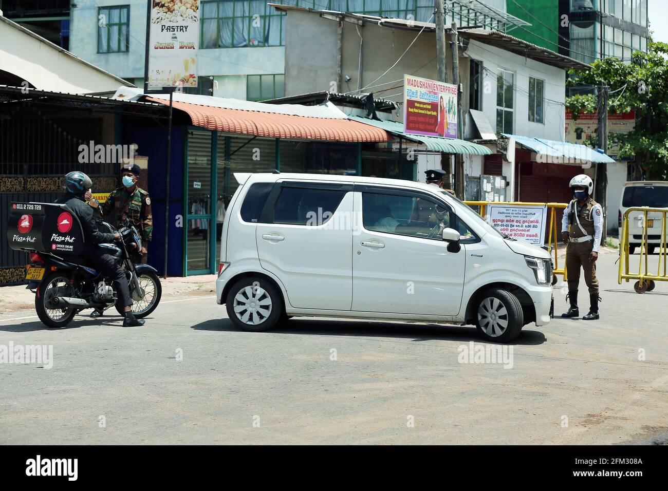 Colombo, Sri Lanka. 5 mai 2021. Des membres de l'armée et de la police sont vus à côté de barricades établies à Maharagama, alors que les autorités sanitaires ont déclaré la zone à isoler, à Colombo, au Sri Lanka, le 5 mai 2021. Le nombre total de patients infectés par le COVID-19 au Sri Lanka a dépassé la barre des 115,000 mercredi après que plus de 1,800 nouveaux patients ont été identifiés un jour plus tôt, ont montré les statistiques du ministère de la Santé. Crédit: Ajith Perera/Xinhua/Alamy Live News Banque D'Images