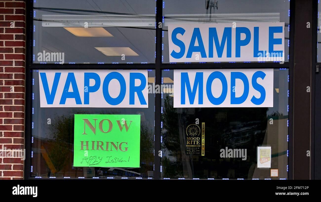 Emporia, Kansas, États-Unis. 6 mai 2021. Des affiches d'embauche sont maintenant affichées à la fenêtre de l'atelier local de fumée Vapor à Emporia, Kansas, alors que les entreprises cherchent à embaucher des employés et à augmenter la production normale après la pandémie de COVID-19, le 6 mai 2021. Crédit : Mark Reinstein/Media Punch/Alamy Live News Banque D'Images